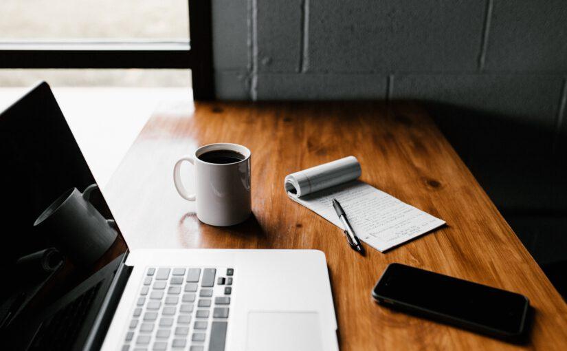 laptop, notes i telefon na stole